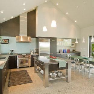 Diseño de cocina en L, exótica, abierta, con armarios con paneles lisos, electrodomésticos de acero inoxidable, encimera de acero inoxidable, puertas de armario de madera en tonos medios, salpicadero azul y encimeras verdes