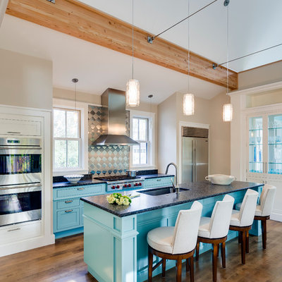 Mid-sized trendy galley dark wood floor open concept kitchen photo in Portland Maine with an island, shaker cabinets, metallic backsplash, stainless steel appliances, an undermount sink, turquoise cabinets, laminate countertops and metal backsplash