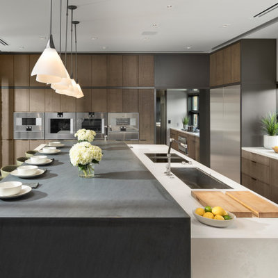 Huge trendy l-shaped porcelain tile and gray floor open concept kitchen photo in Las Vegas with an undermount sink, flat-panel cabinets, quartz countertops, stainless steel appliances, an island, white countertops, medium tone wood cabinets and window backsplash