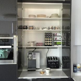 Modern inredning av ett stort kök, med grå skåp, en köksö, en enkel diskho, släta luckor, bänkskiva i kvarts, flerfärgad stänkskydd, stänkskydd i glaskakel, rostfria vitvaror och klinkergolv i porslin