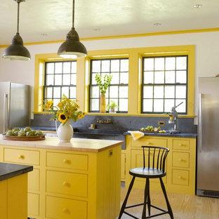 Imagen de cocina campestre con fregadero sobremueble, armarios con rebordes decorativos, puertas de armario amarillas, salpicadero verde, electrodomésticos de acero inoxidable, suelo de madera clara y dos o más islas