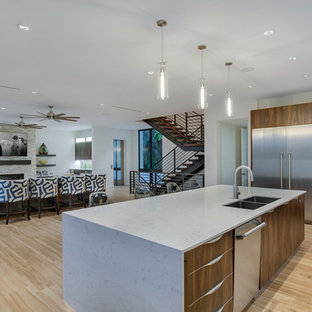 Design ideas for a mid-sized modern l-shaped open plan kitchen in Tampa with a double-bowl sink, flat-panel cabinets, dark wood cabinets, quartz benchtops, yellow splashback, glass tile splashback, stainless steel appliances, porcelain floors, with island, brown floor and white benchtop.