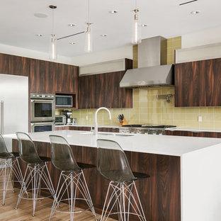 Стильный дизайн: угловая кухня среднего размера в современном стиле с двойной раковиной, плоскими фасадами, темными деревянными фасадами, столешницей из кварцевого композита, желтым фартуком, фартуком из стеклянной плитки, техникой из нержавеющей стали, полом из керамогранита, островом, коричневым полом и белой столешницей - последний тренд