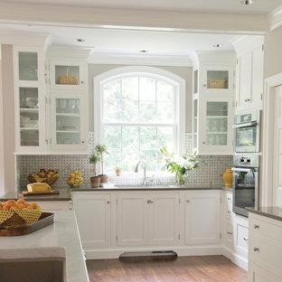 На фото: кухня в классическом стиле с стеклянными фасадами, белыми фасадами, столешницей из кварцевого агломерата, фартуком из каменной плитки и разноцветным фартуком с