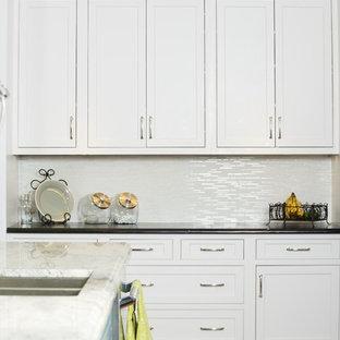 Пример оригинального дизайна: большая угловая кухня в стиле современная классика с белыми фасадами, столешницей из талькохлорита, белым фартуком, фартуком из стеклянной плитки, техникой из нержавеющей стали, паркетным полом среднего тона, островом, обеденным столом и коричневым полом