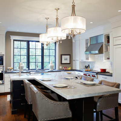 Example of a large classic l-shaped dark wood floor enclosed kitchen design in Philadelphia with subway tile backsplash, paneled appliances, a farmhouse sink, shaker cabinets, white cabinets, marble countertops, white backsplash and an island