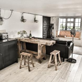 Bild på ett litet industriellt kök, med en rustik diskho, skåp i shakerstil, svarta skåp, granitbänkskiva, vitt stänkskydd, stänkskydd i cementkakel, integrerade vitvaror, ljust trägolv och en halv köksö