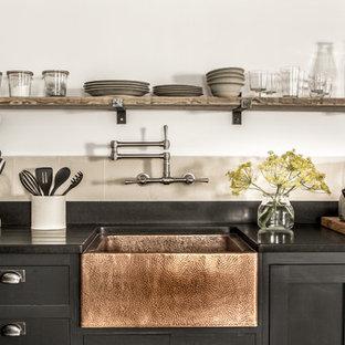 Industriell inredning av ett litet l-kök, med en rustik diskho, svarta skåp, granitbänkskiva, stänkskydd i cementkakel och öppna hyllor