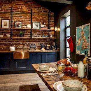 他の地域の中くらいのエクレクティックスタイルのおしゃれなキッチン (無垢フローリング、茶色い床、三角天井、エプロンフロントシンク、シェーカースタイル扉のキャビネット、黒いキャビネット、木材カウンター、レンガのキッチンパネル、アイランドなし、茶色いキッチンカウンター) の写真