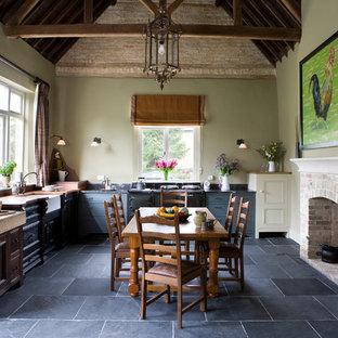 Foto di una grande cucina country con lavello stile country, ante con riquadro incassato, ante grigie, pavimento in ardesia, nessuna isola e elettrodomestici neri