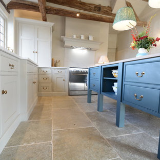 Large country u-shaped open plan kitchen in Sussex with beaded inset cabinets, beige cabinets, quartzite benchtops, white splashback, panelled appliances, limestone floors, with island, white benchtop, an integrated sink and green floor.