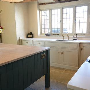 サセックスの大きいカントリー風おしゃれなキッチン (インセット扉のキャビネット、ベージュのキャビネット、珪岩カウンター、白いキッチンパネル、パネルと同色の調理設備、ライムストーンの床、白いキッチンカウンター、一体型シンク、緑の床) の写真