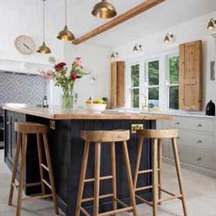 ハートフォードシャーの中サイズのカントリー風おしゃれなキッチン (アンダーカウンターシンク、落し込みパネル扉のキャビネット、グレーのキャビネット、木材カウンター、白いキッチンパネル、シルバーの調理設備の、グレーの床、ベージュのキッチンカウンター) の写真
