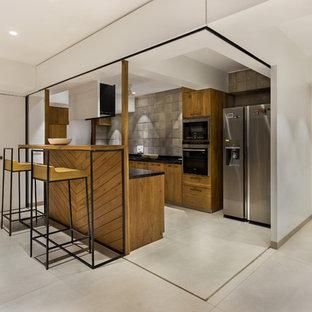Idee per una cucina ad U design di medie dimensioni con ante in legno scuro e elettrodomestici in acciaio inossidabile