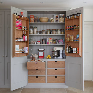 Diseño de cocina campestre con despensa y puertas de armario grises