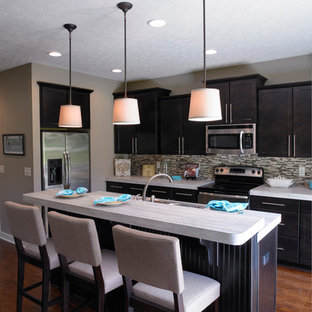 This is an example of a small arts and crafts l-shaped open plan kitchen in Other with shaker cabinets, dark wood cabinets, stainless steel appliances, with island, laminate benchtops, a drop-in sink, multi-coloured splashback, matchstick tile splashback, dark hardwood floors and brown floor.