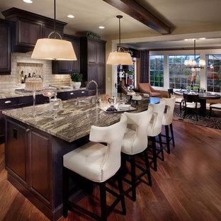 Mediterranean eat-in kitchen inspiration - Example of a tuscan eat-in kitchen design in Denver with a double-bowl sink, raised-panel cabinets, dark wood cabinets, beige backsplash and subway tile backsplash
