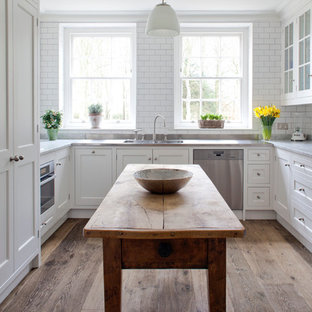 Photo of a traditional u-shaped separate kitchen in Wiltshire with recessed-panel cabinets, white cabinets, marble benchtops, white splashback, subway tile splashback and stainless steel appliances.