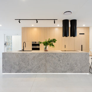 Large contemporary galley open plan kitchen in Brisbane with an undermount sink, light wood cabinets, limestone benchtops, black appliances, marble floors, with island, white floor, grey benchtop and flat-panel cabinets.