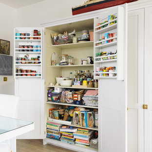 Photo Of A Country Kitchen Pantry With Shaker Cabinets, White Cabinets,  Light Hardwood Flooring