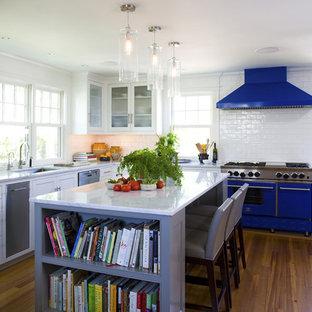 Mittelgroße Maritime Küche in U-Form mit Glasfronten, Rückwand aus Metrofliesen, bunten Elektrogeräten, Unterbauwaschbecken, weißen Schränken, Küchenrückwand in Weiß, braunem Holzboden, Kücheninsel und braunem Boden in Boston