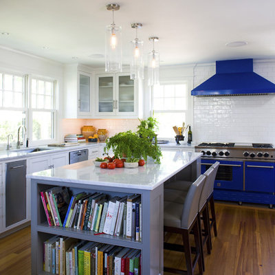 Kitchen - mid-sized coastal u-shaped medium tone wood floor and brown floor kitchen idea in Boston with glass-front cabinets, subway tile backsplash, colored appliances, an undermount sink, white cabinets, white backsplash and an island