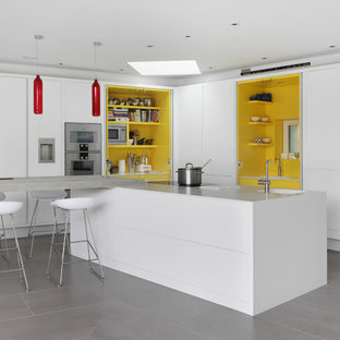 Photo of a mid-sized contemporary l-shaped eat-in kitchen in London with a drop-in sink, flat-panel cabinets, white cabinets, laminate benchtops, yellow splashback, stainless steel appliances, porcelain floors and multiple islands.