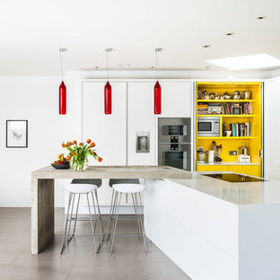 Photo of a contemporary kitchen in London with flat-panel cabinets, white cabinets, stainless steel appliances and an island.
