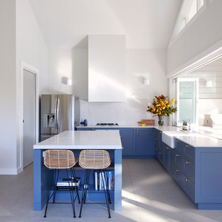 Design ideas for a transitional l-shaped kitchen in Sydney with shaker cabinets, blue cabinets, with island, a farmhouse sink, white splashback, stainless steel appliances and grey floor.