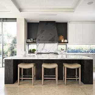 This is an example of an expansive beach style l-shaped open plan kitchen in Sydney with louvered cabinets, white cabinets, marble benchtops, stone slab splashback, stainless steel appliances, limestone floors and with island.