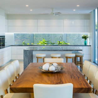 This is an example of a contemporary l-shaped eat-in kitchen in Cairns with an undermount sink, granite benchtops, white splashback, glass sheet splashback, stainless steel appliances, porcelain floors, with island, white floor, grey benchtop, flat-panel cabinets and white cabinets.