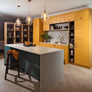 他の地域の広いコンテンポラリースタイルのおしゃれなキッチン (シングルシンク、フラットパネル扉のキャビネット、黄色いキャビネット、人工大理石カウンター、グレーのキッチンパネル、セラミックタイルのキッチンパネル、パネルと同色の調理設備、合板フローリング、白い床、白いキッチンカウンター) の写真