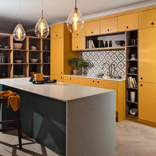 Large contemporary open plan kitchen in Other with a single-bowl sink, flat-panel cabinets, yellow cabinets, composite countertops, grey splashback, ceramic splashback, integrated appliances, plywood flooring, an island, white floors and white worktops.