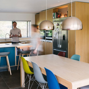 This is an example of a scandi l-shaped kitchen/diner in Other with a submerged sink, flat-panel cabinets, light wood cabinets, stainless steel appliances, an island, brown floors and white worktops.