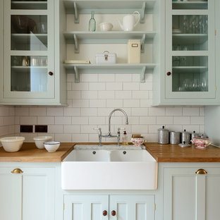 Design ideas for a medium sized classic single-wall enclosed kitchen in London with beaded cabinets, blue cabinets, wood worktops, white splashback, metro tiled splashback, stainless steel appliances, light hardwood flooring, no island and a double-bowl sink.