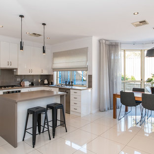 Scandinavian l-shaped eat-in kitchen in Adelaide with a drop-in sink, flat-panel cabinets, white cabinets, beige splashback, glass sheet splashback, stainless steel appliances, with island, white floor and beige benchtop.
