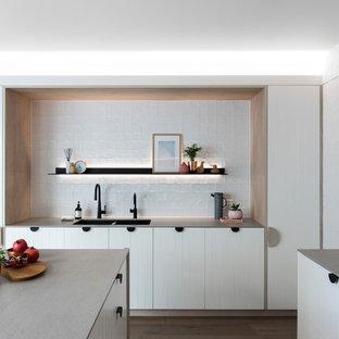 Offene, Mittelgroße Moderne Küche in L-Form mit Doppelwaschbecken, weißen Schränken, Arbeitsplatte aus Recyclingglas, Küchenrückwand in Weiß, Rückwand aus Zementfliesen, schwarzen Elektrogeräten, braunem Holzboden, Kücheninsel und grauer Arbeitsplatte in Sydney