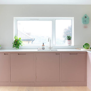 This is an example of a mid-sized scandinavian l-shaped eat-in kitchen in Other with flat-panel cabinets, pink cabinets, quartz benchtops, light hardwood floors, no island and white benchtop.