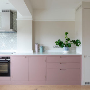 Mid-sized scandinavian l-shaped eat-in kitchen in Other with flat-panel cabinets, pink cabinets, quartz benchtops, light hardwood floors, no island and white benchtop.