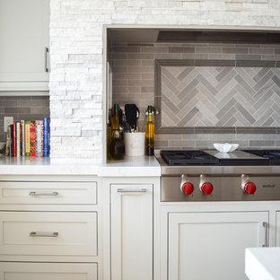ニューヨークの中サイズのビーチスタイルのおしゃれなキッチン (アンダーカウンターシンク、シェーカースタイル扉のキャビネット、グレーのキャビネット、クオーツストーンカウンター、グレーのキッチンパネル、スレートのキッチンパネル、パネルと同色の調理設備、無垢フローリング) の写真