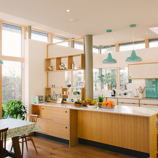 Large midcentury u-shaped open plan kitchen in Manchester with flat-panel cabinets, white cabinets, composite countertops, blue splashback, glass sheet splashback, stainless steel appliances, no island and white worktops.