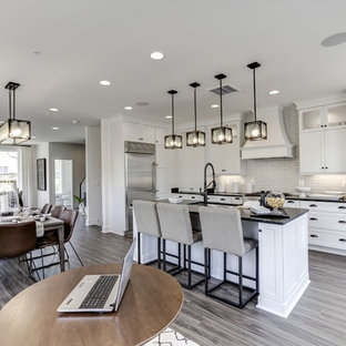 Large transitional open plan kitchen in DC Metro with an undermount sink, shaker cabinets, white cabinets, granite benchtops, grey splashback, ceramic splashback, stainless steel appliances, vinyl floors, with island, grey floor and black benchtop.