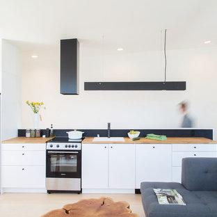 Offene, Einzeilige, Kleine Moderne Küche ohne Insel mit Waschbecken, flächenbündigen Schrankfronten, weißen Schränken, Arbeitsplatte aus Holz, Küchenrückwand in Schwarz, weißen Elektrogeräten, Sperrholzboden, weißem Boden und brauner Arbeitsplatte in Seattle