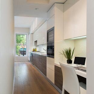 Diseño de cocina lineal, actual, pequeña, abierta, sin isla, con armarios con paneles lisos, puertas de armario blancas, suelo de madera en tonos medios, fregadero bajoencimera, encimera de cuarzo compacto, salpicadero blanco, salpicadero de azulejos de vidrio y electrodomésticos de acero inoxidable