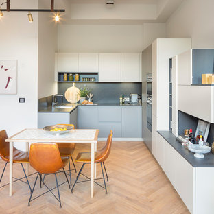 Contemporary u-shaped kitchen/diner in London with a submerged sink, flat-panel cabinets, grey cabinets, grey splashback, integrated appliances, light hardwood flooring, no island, beige floors and grey worktops.