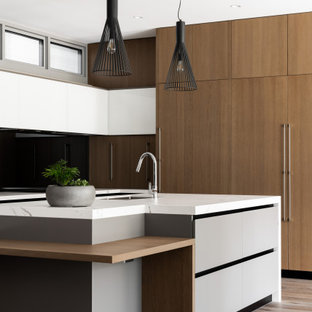 This is an example of a contemporary kitchen in Perth with an undermount sink, flat-panel cabinets, medium wood cabinets, panelled appliances, medium hardwood floors, with island, grey floor and white benchtop.