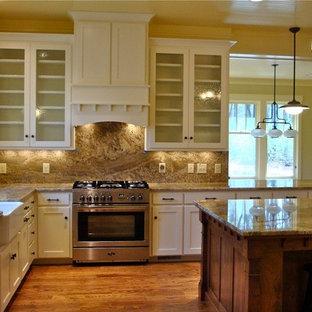 他の地域のトラディショナルスタイルのおしゃれなキッチン (エプロンフロントシンク、ルーバー扉のキャビネット、中間色木目調キャビネット、ソープストーンカウンター、ベージュキッチンパネル、シルバーの調理設備) の写真