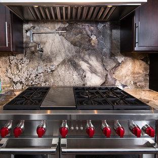 デンバーの広いコンテンポラリースタイルのおしゃれなキッチン (アンダーカウンターシンク、フラットパネル扉のキャビネット、濃色木目調キャビネット、御影石カウンター、ベージュキッチンパネル、石スラブのキッチンパネル、シルバーの調理設備、濃色無垢フローリング、アイランドなし) の写真