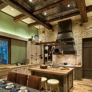 Huge rustic kitchen pantry ideas - Inspiration for a huge rustic galley medium tone wood floor kitchen pantry remodel in Phoenix with a farmhouse sink, recessed-panel cabinets, distressed cabinets, concrete countertops, green backsplash, glass sheet backsplash, paneled appliances and an island