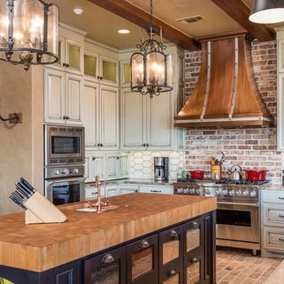 Photo of a country u-shaped kitchen in Austin with raised-panel cabinets, white cabinets, wood benchtops, white splashback, window splashback, stainless steel appliances, brick floors, with island and brown floor.